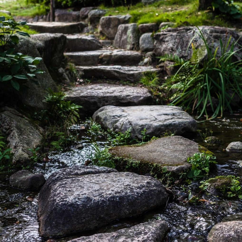 Zen stone pathway over a stream in a traditional Japanese garden somewhere in Tokyo