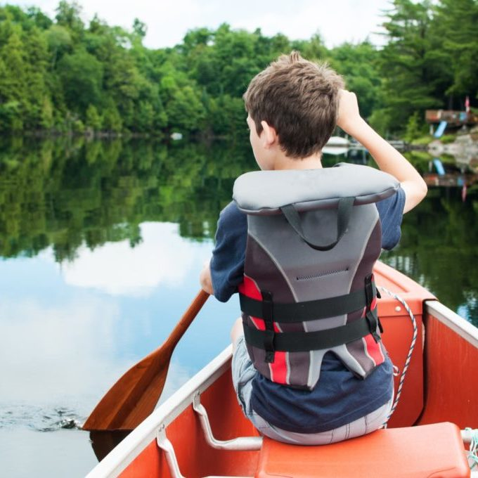 young boy paddling in a calm lake in the front of a canoe